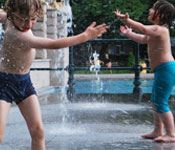 Two boys playing in water fountain